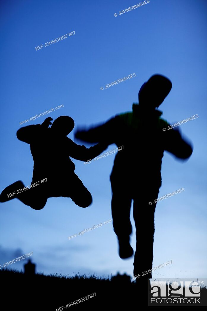 Stock Photo: Silhouette of two people jumping.