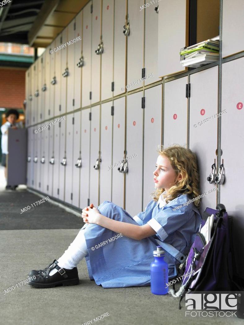 Stock Photo: Elementary schoolgirl sitting on floor against school lockers.