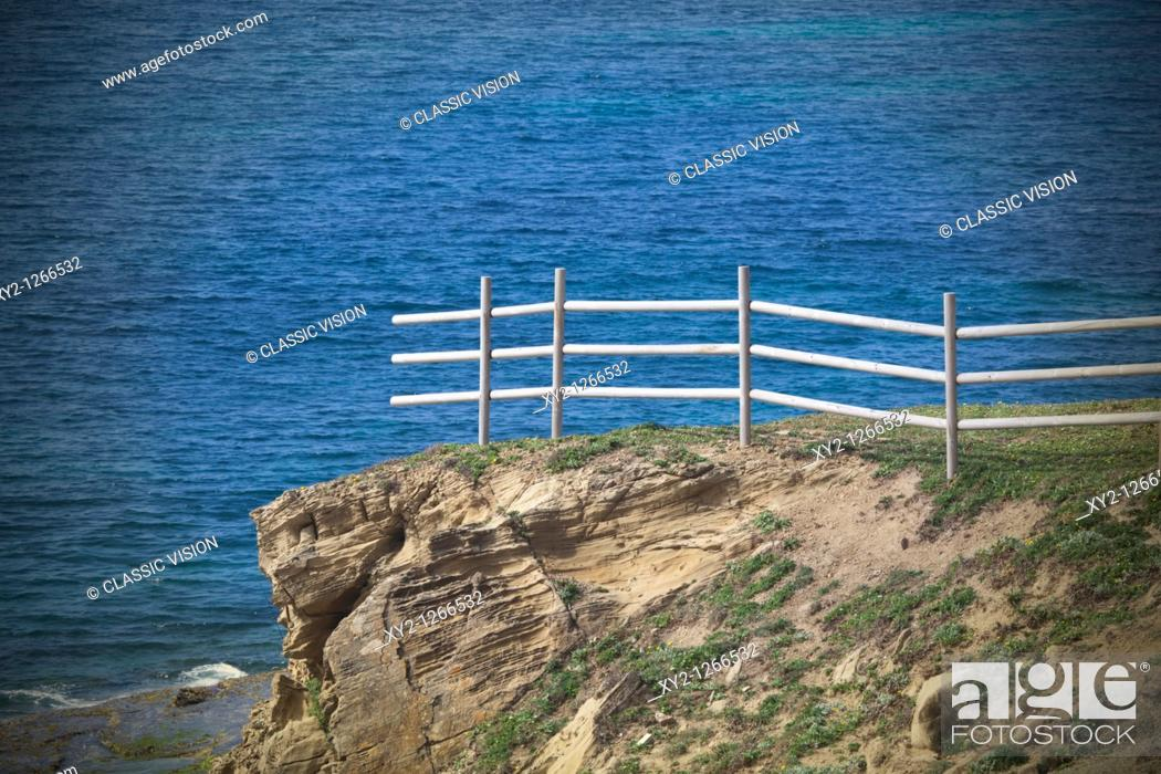Stock Photo: Unfinished fence on cliff above ocean.