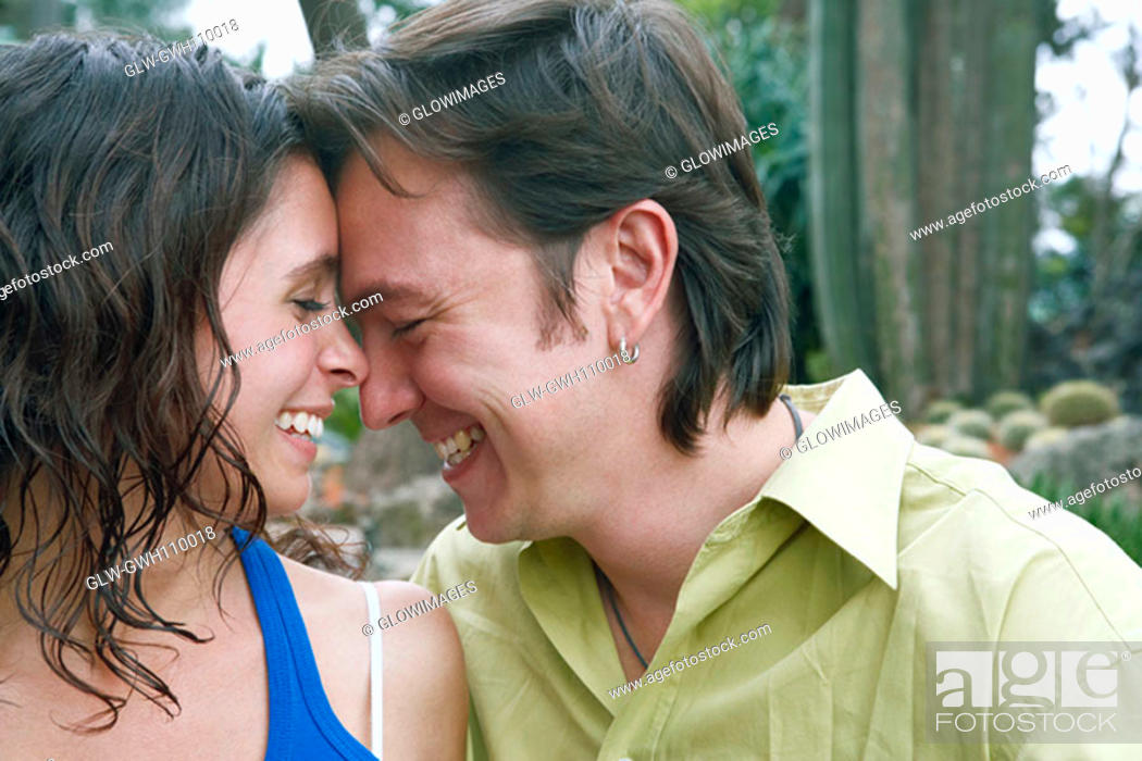 Stock Photo: Close-up of a young woman and a mid adult man smiling in a park.