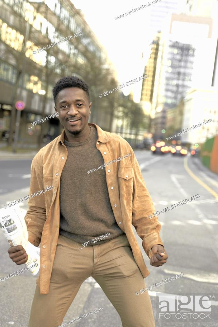 Stock Photo: motivated African man with newspaper on street in city, in Frankfurt, Germany.