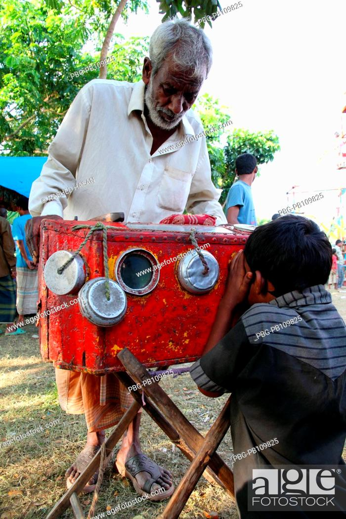 A child watching bioscope at a fair or mela set up around