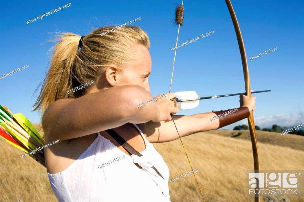 Stock Photo: Young woman arrow shooting.