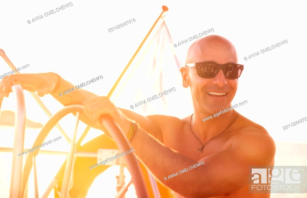 Stock Photo: Portrait of handsome shirtless sailor behind helm of sailboat in bright sunny day, enjoying active summer holidays, happy traveling along sea.