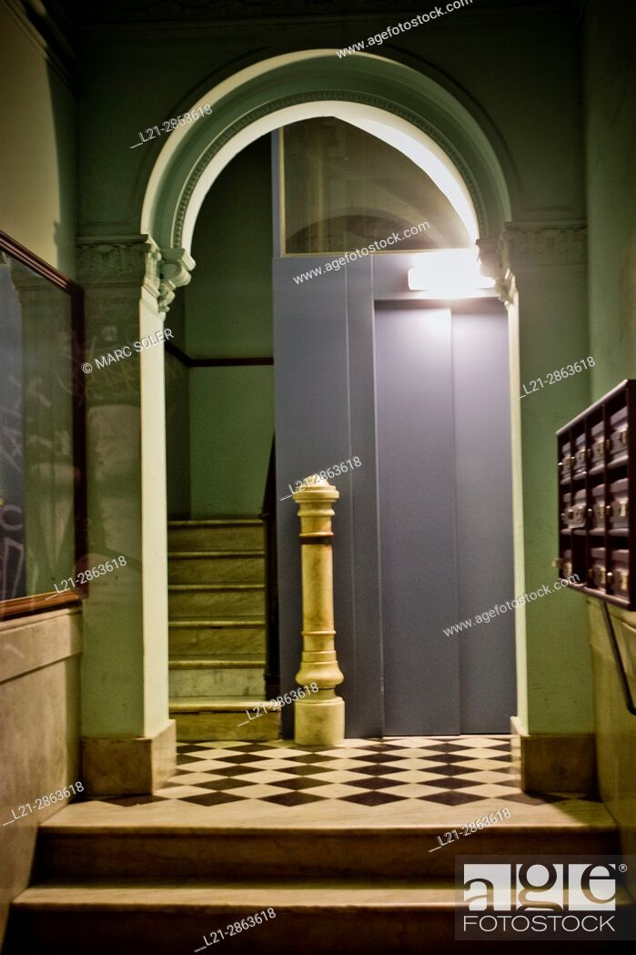 Stock Photo: Entrance of a residential house at night. Interior with light, corridor, stairs and elevator. Barcelona, Catalonia, Spain.