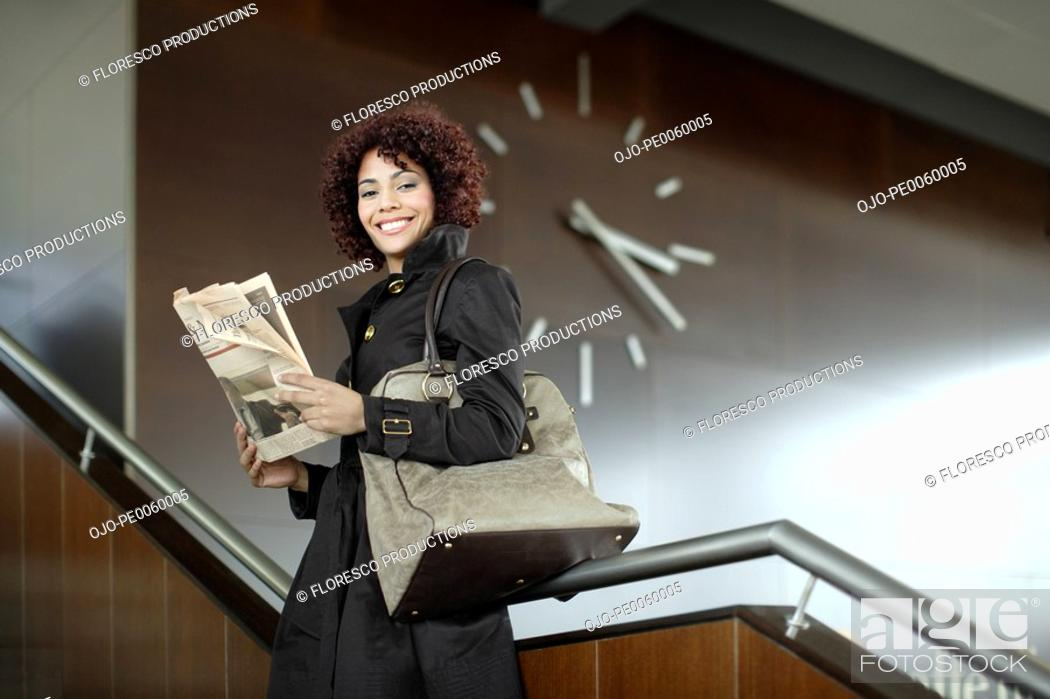 Stock Photo: Businesswoman indoors on staircase with newspaper.