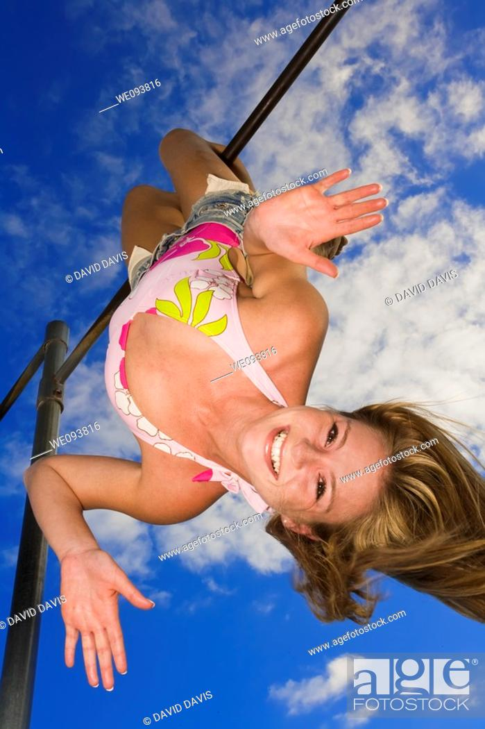 Stock Photo: Beautiful Caucasian female teenage hanging upside down on outdoor gym bar and wearing a swimsuit.