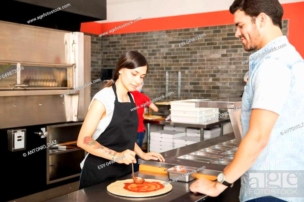 Stock Photo: Woman chef wearing apron applying tomato sauce over dough pizza bread while customer looking at pizza.