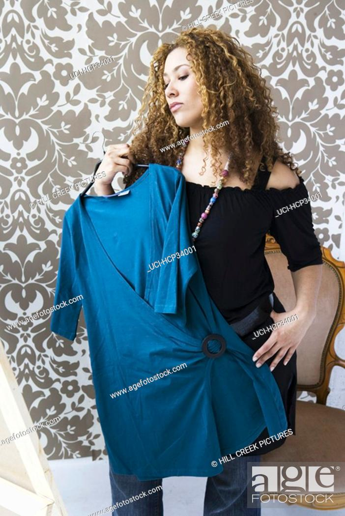 Stock Photo: Woman holding blouse in front of mirror.