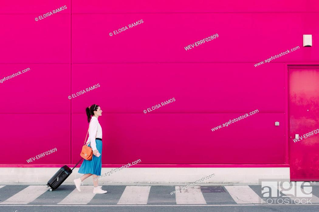 Stock Photo: Young woman using smartphone and walking with trolley along a pink wall.