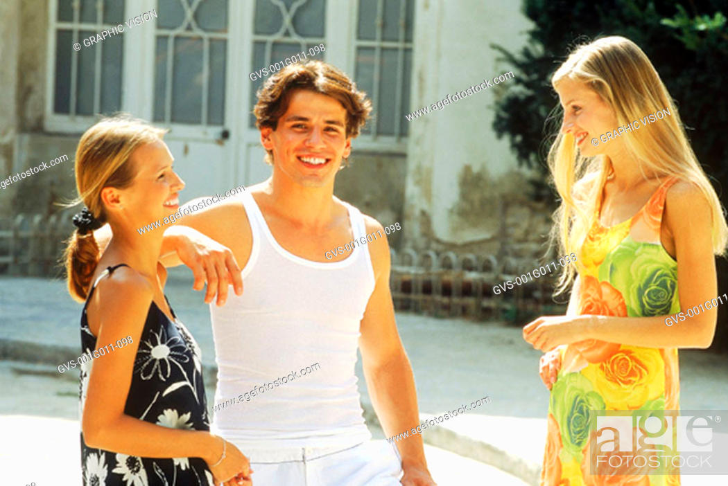 Stock Photo: Two young women talking to a man outdoors.