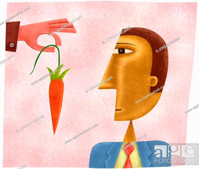 Stock Photo: A hand dangling a carrot in front of a business mans face.