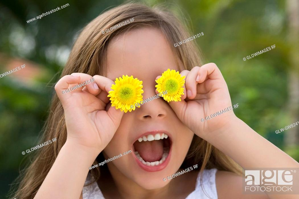 Stock Photo: Close-up of a girl holding flowers over her eyes.
