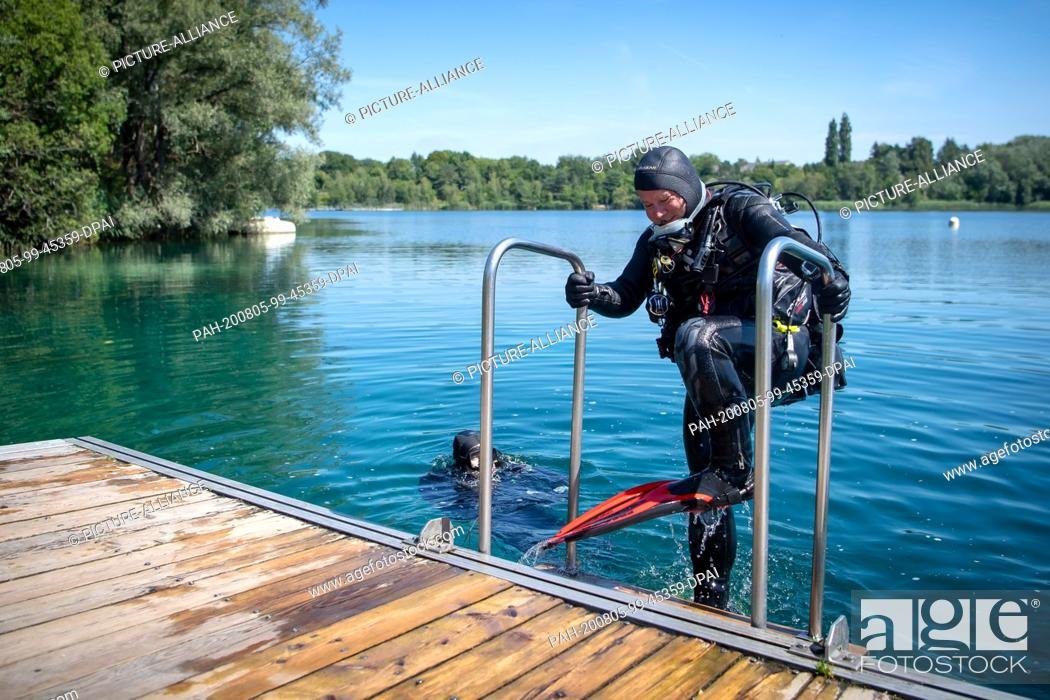 Stock Photo: 31 July 2020, Lower Saxony, Hemmoor: Dirk Pedina climbs out of the chalk lake after diving. The lake in the district of Cuxhaven is also popular with divers.