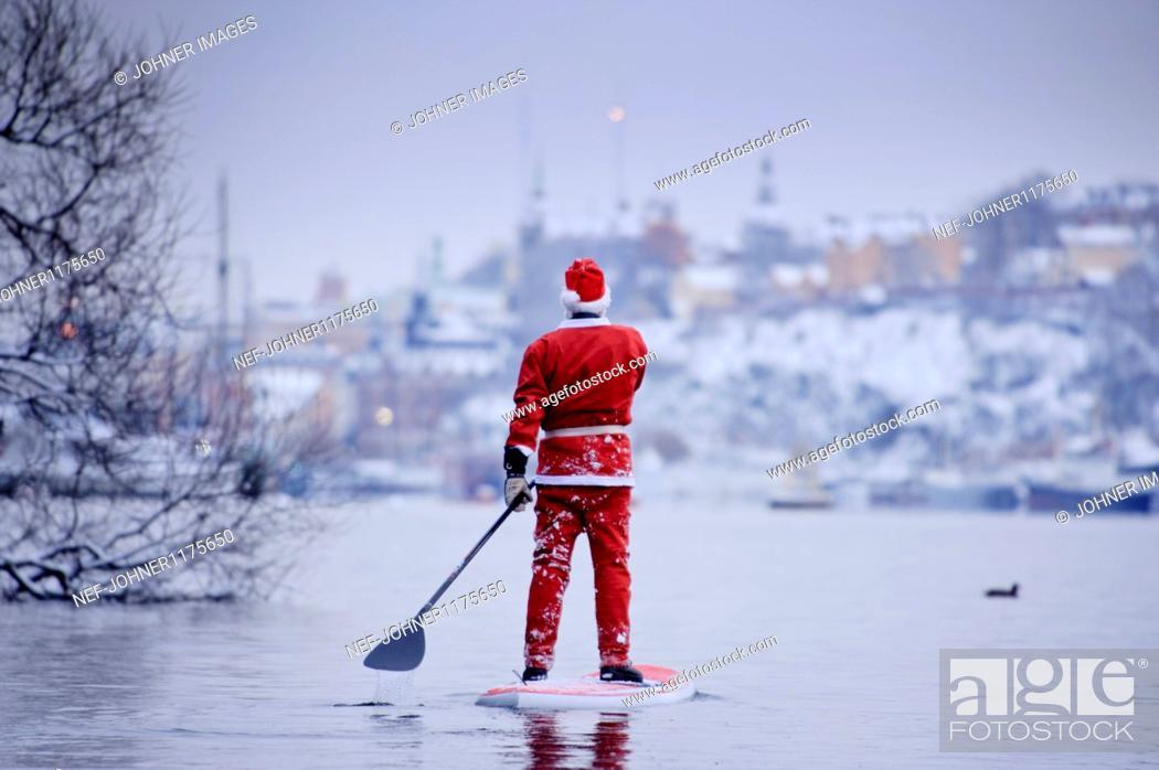 Stock Photo: Man dressed as Santa Claus paddling on lake.