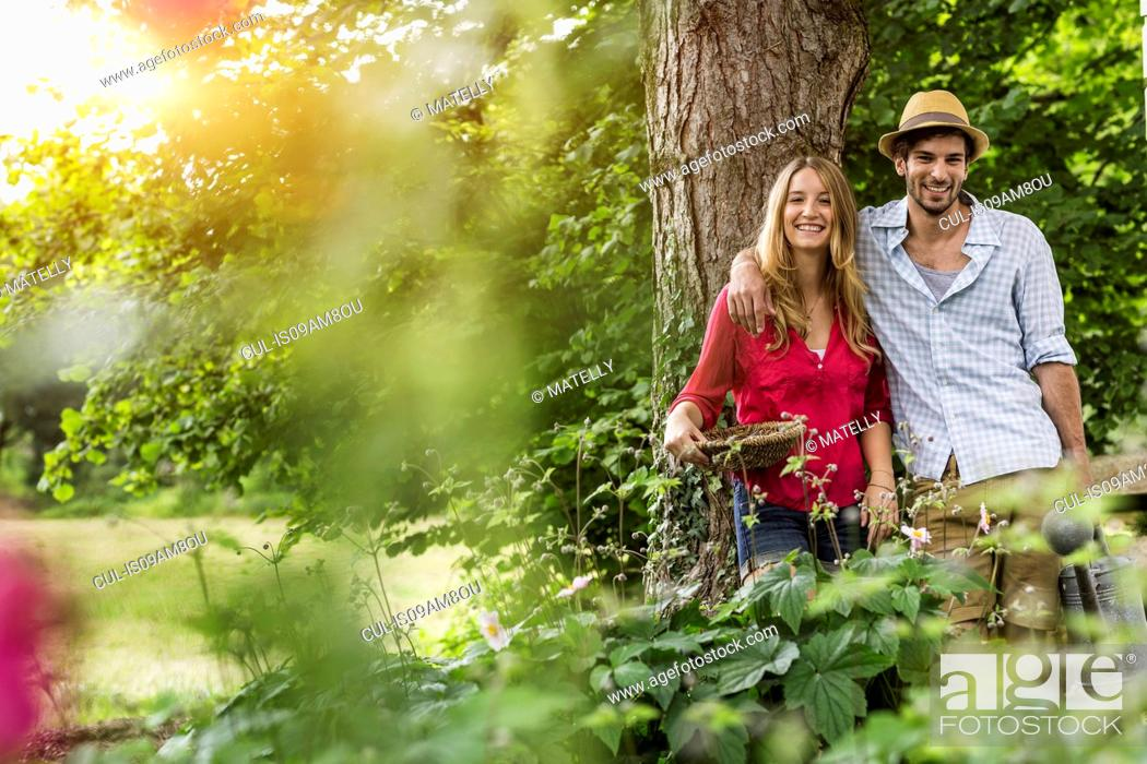 Stock Photo: Portrait of young couple with flower basket in garden.