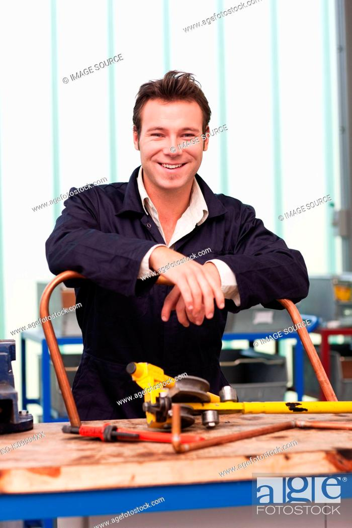 Stock Photo: Plumber with copper pipe in workshop, portrait.