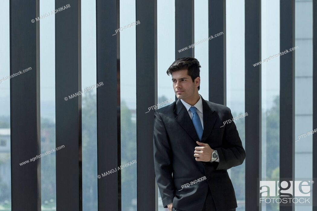 Stock Photo: India, Man in suit standing outside building.