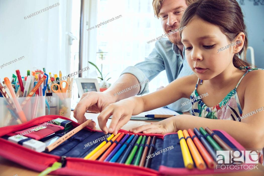 Stock Photo: Father helping girl doing her schoolwork at home.