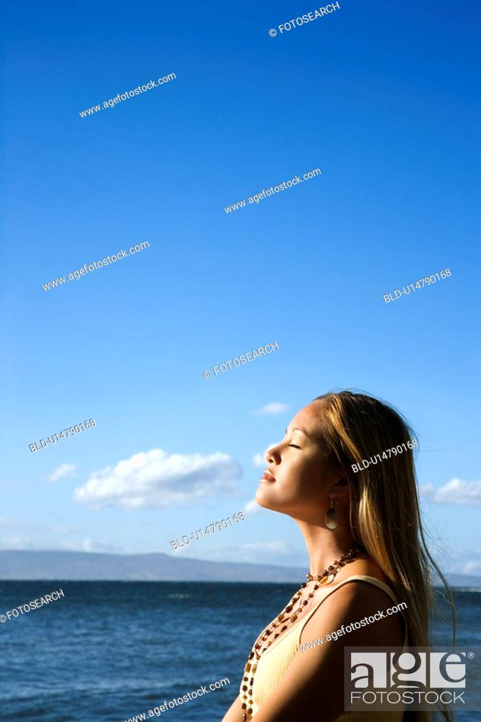 Stock Photo: Young adult female standing on beach.