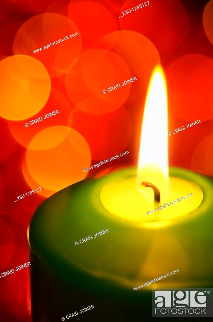 Stock Photo: A green candle burning with fairy lights in the background out of focus.