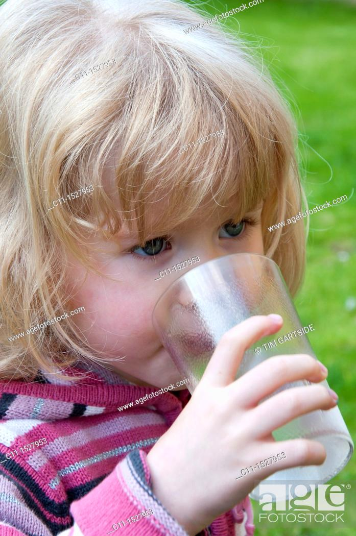 Stock Photo: Young three year old girl drinking water.