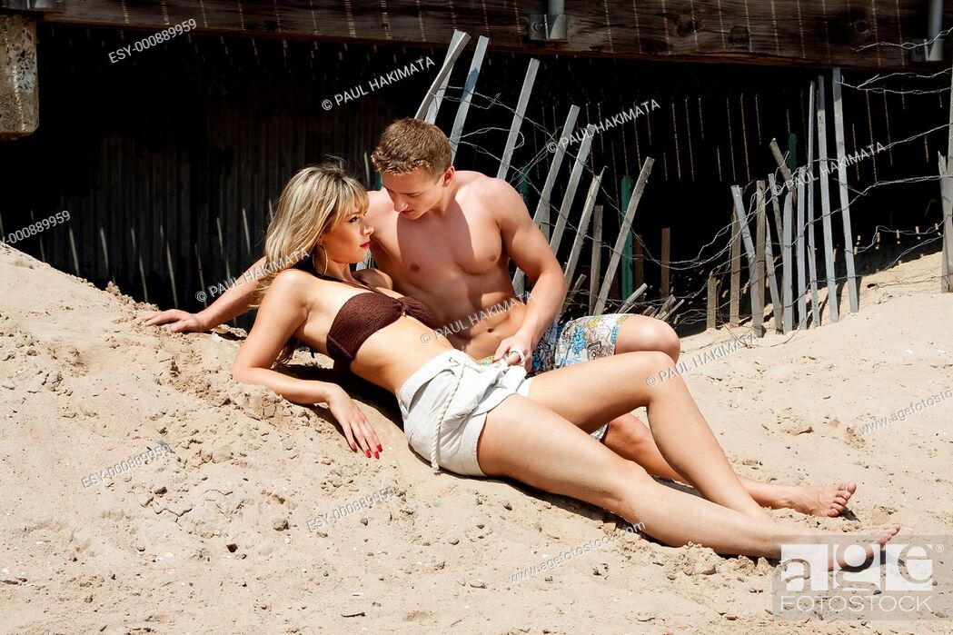 Stock Photo: Beautiful sexy fashion couple, guy and girl, wearing bathing clothes while at the beach  both laying romantically on the sand in front of the boardwalk.