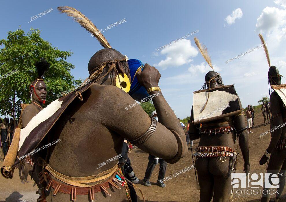Stock Photo: Bodi tribe fat men drinking milk during the Kael ceremony, Omo valley, Hana Mursi, Ethiopia.