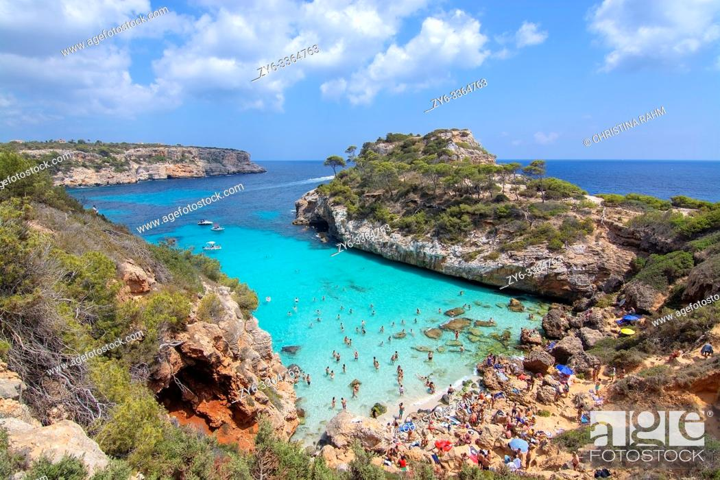 Stock Photo: CALO DES MORO, MALLORCA, SPAIN - JULY 27, 2019: Small extremely turquoise bay and steep cliffs on a sunny day on July 27, 2019 in Calo des Moro, Mallorca, Spain.