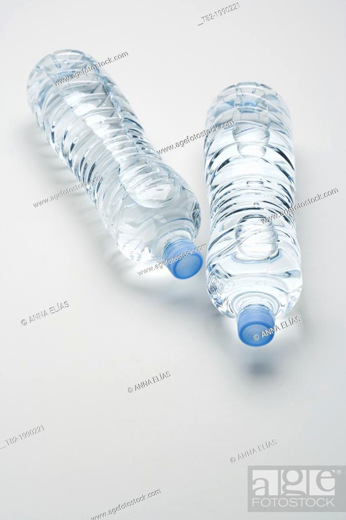 Stock Photo: two bottles of mineral water lying without label on white background.