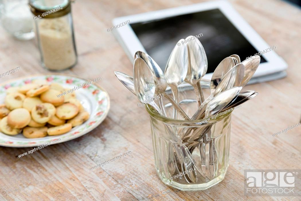 Stock Photo: Digital tablet, plate of cookies and jar of spoons on wooden surface.