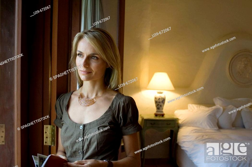 Stock Photo: Beautiful woman standing next to a window.