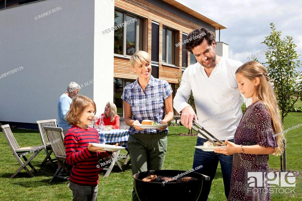 Stock Photo: Germany, Bavaria, Nuremberg, Family barbucue in garden.