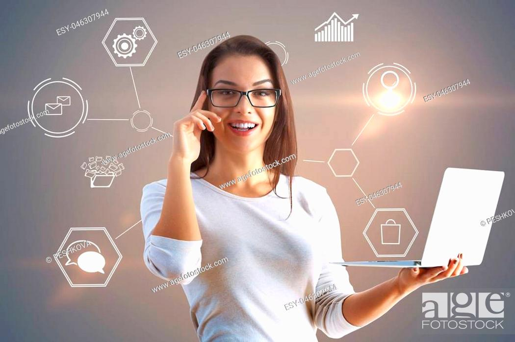 Stock Photo: smiling businesswoman with glasses holding laptop at global social network background.