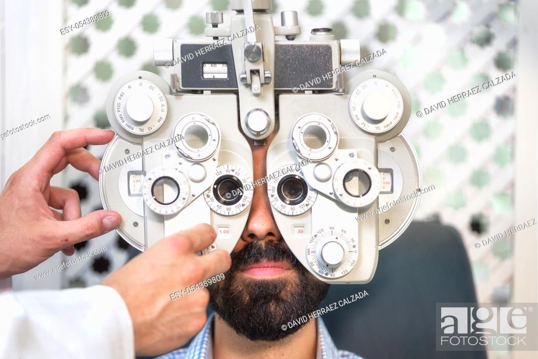 Stock Photo: Optometrist doing sight testing for male patient In clinic. Male ophthalmologist examining patient man with optometrist trial frame .