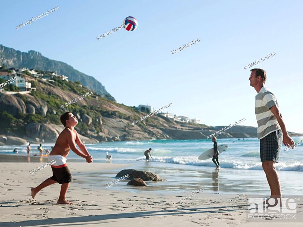 Stock Photo: Father and son playing ball on a beach.