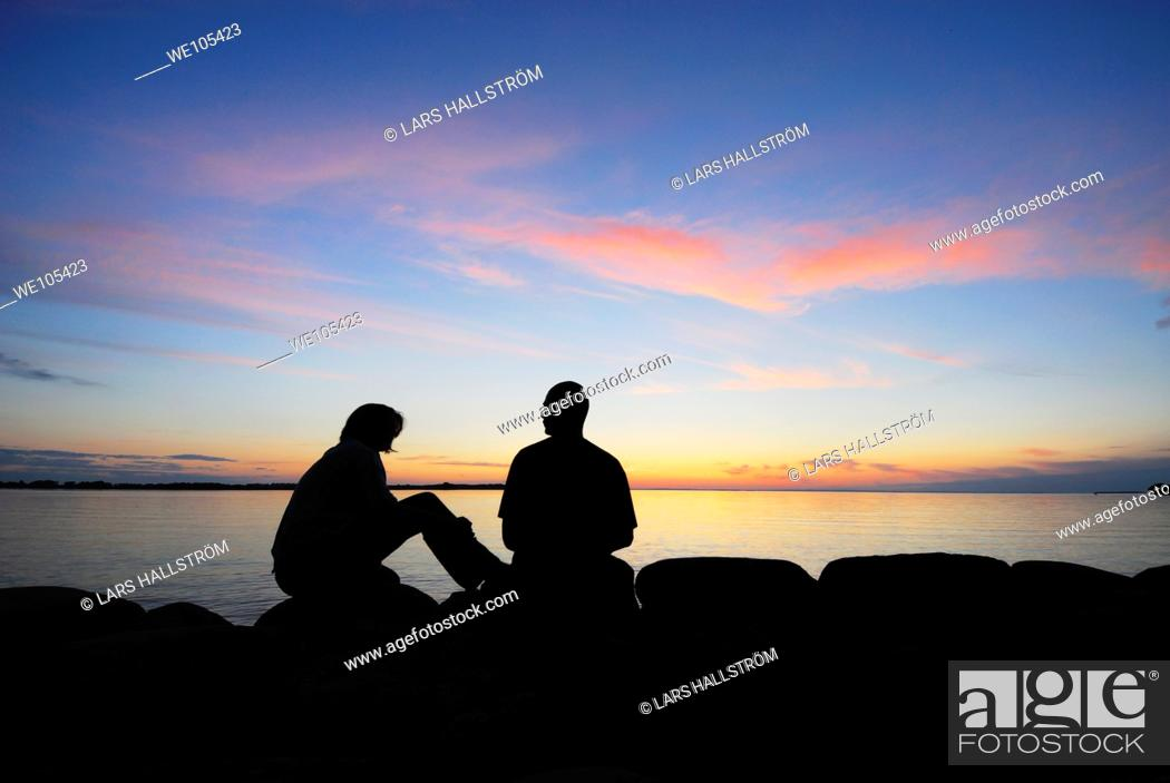 Stock Photo: Silhouette of a couple by a lake at sunset, Sweden.