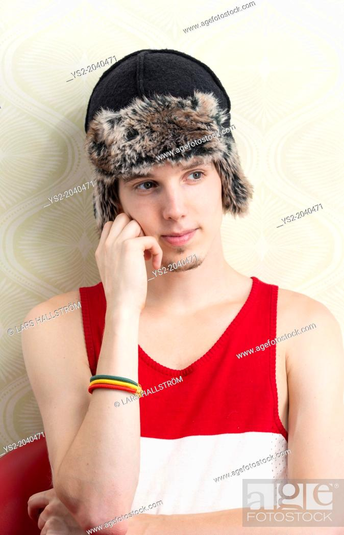 Stock Photo: Lifestyle portrait of serious young man with winter hat and tank top.