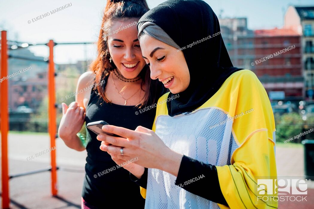 Stock Photo: Calisthenics class at outdoor gym, two young women looking at smartphone.