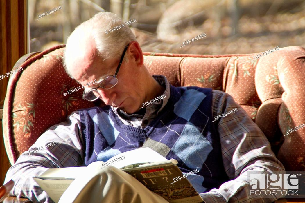 Stock Photo: older man in glasses falling asleep in armchair in sunshine while reading, Monroe County, Indiana.