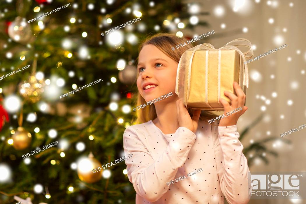 Stock Photo: smiling girl with christmas gift at home.