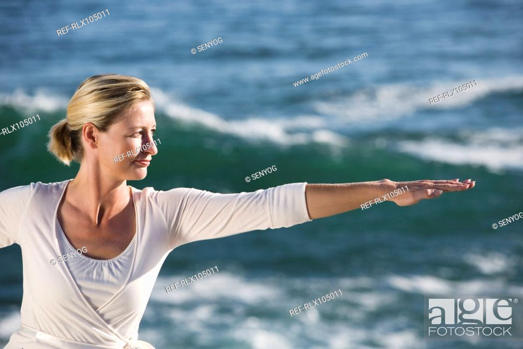 Stock Photo: Mature woman with arms outstretched, with waves breaking in background.