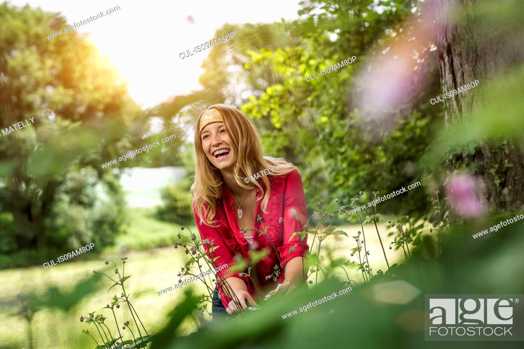 Stock Photo: Young woman laughing whilst cutting flowers in garden.