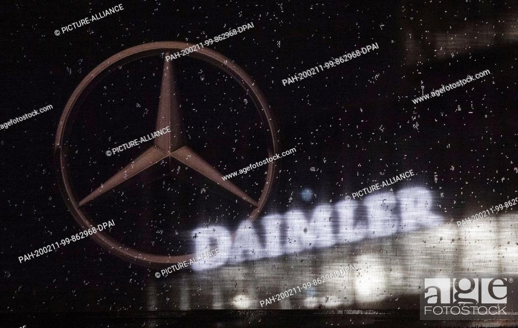 Stock Photo: 11 February 2020, Baden-Wuerttemberg, Stuttgart: The logo of the Daimler AG can be seen at the corporate headquarters, in the foreground a Mercedes star is.