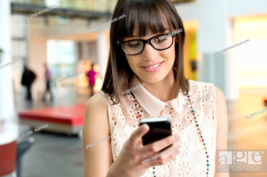 Stock Photo: Businesswoman text messaging in an office.
