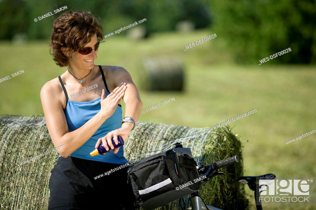 Stock Photo: Germany, Bavaria, Seeshaupt, Woman with mountain bike applying sun cream.