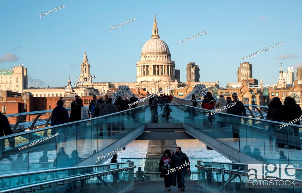 Stock Photo: London, United Kingdom - December 8 2015: People walking at the Millennium bridge , officially known as the London Millennium Footbridge crossing river Thames.