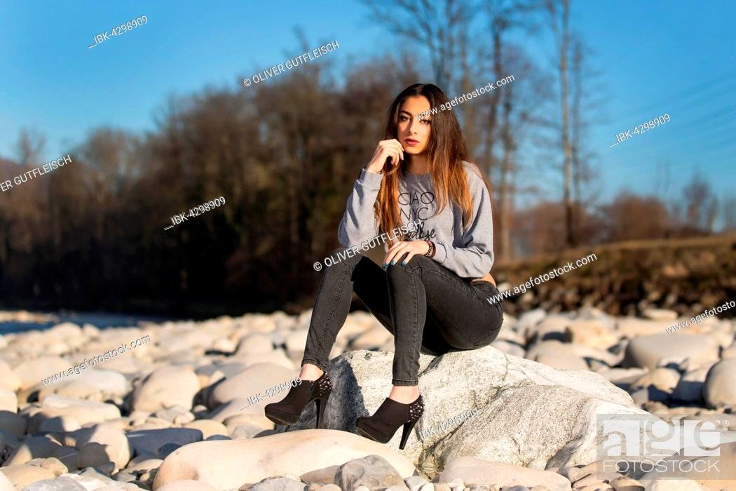 Stock Photo: Young woman with long brunette hair sits on stone in dry river in winter, fashion, look into the camera.