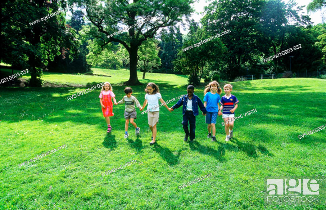 Stock Photo: Young children holding hands walking on a lawn.