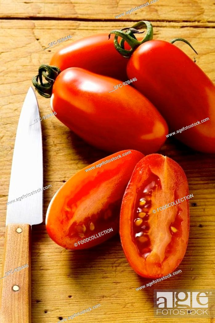 Stock Photo: Four 'date' tomatoes on wooden background, one halved.
